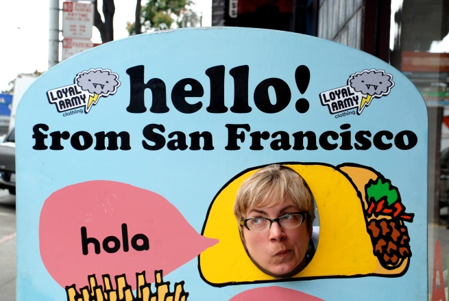 Chris making use of a sidewalk sign on Haight Street.