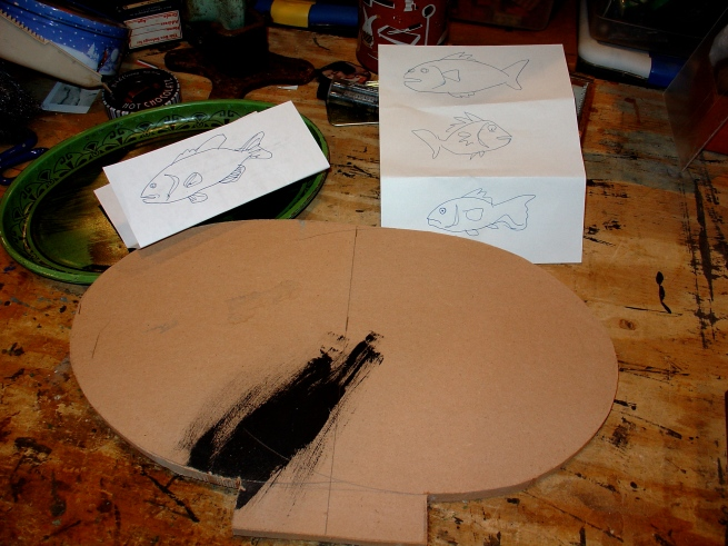 I began with a few thumbnail sketches of fish, and then cut an oval base out of MDF.