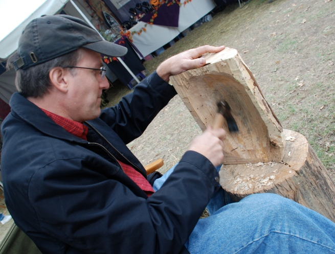 Jim Haizlett working on a wood bowl in front of his booth.
