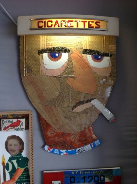 """Cigarette Head"", by Robert Villamagna, made using a sign from a vintage cigarette sign, along with repurposed metal product containers."