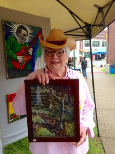 Artist Liz Neuman shows off a pastel painting that she purchased from Bob Sako.